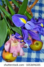 Close-up of spring flowers, iris and Peruvian lilies, apples, in the basket on the blue-white checked tablecloth