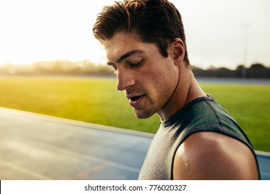 Closeup of a sprinter standing on a running track. Runner looking down standing on the track with sweat dripping from face.