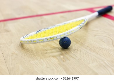 Closeup of a squash racket and ball on the wooden background. Photo with selective focus