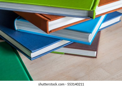 Closeup Stack of colorful books on wooden table . Time to learn and read concept.