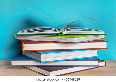 Closeup Stack of colorful books and open book on wooden table with blue background. Time to learn and read concept.