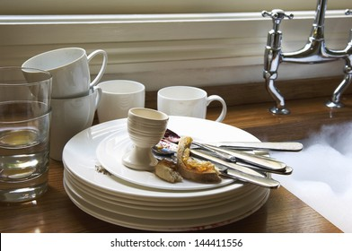 Closeup of a stack of dirty dishes and silverware by sink in the kitchen