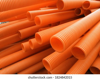 Closeup of stacked orange corrugated PVC plastic pipes, lying on ground in construction site.
