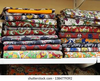 Closeup of stacks of colorful Kalamkari sarees on racks in a textile shop.