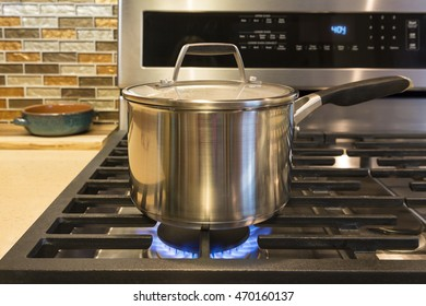 Close-up of stainless steel cooking pot on gas stove in contemporary upscale home kitchen. Selective focus on pot.
