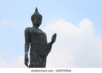 Closeup of standing buddha image in the position of persuading the relatives not to quarrel with cloudy sky backghround. Thailand. Symbol of peaceful.