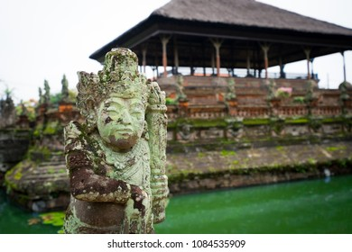 Closeup of a statue of a guardian in a traditional garden with temple and pond in the background, Bali, Indonesia