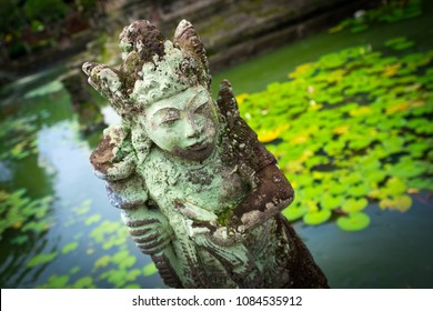 Closeup of a statue of a guardian in a traditional garden with  pond in the background, Bali, Indonesia