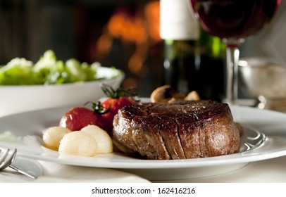 Closeup of a steak with vegetables in a restaurant setting.