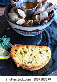 Closeup of steamed clams with melted butter and bread in a bowl