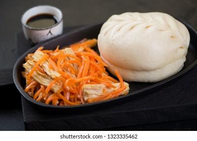 Close-up of steamed korean pjanse or pigodi with carrot and asparagus salad, selective focus, studio shot