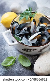 Closeup of steamed mussels with cheese sauce, lemon and parsley. Vertical shot on a grey stone surface with pebbles