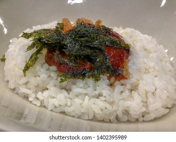 Closeup steamed rice Korea's chili paste (gochujang) on with  dried seaweed on top in cream white ceramic bowl