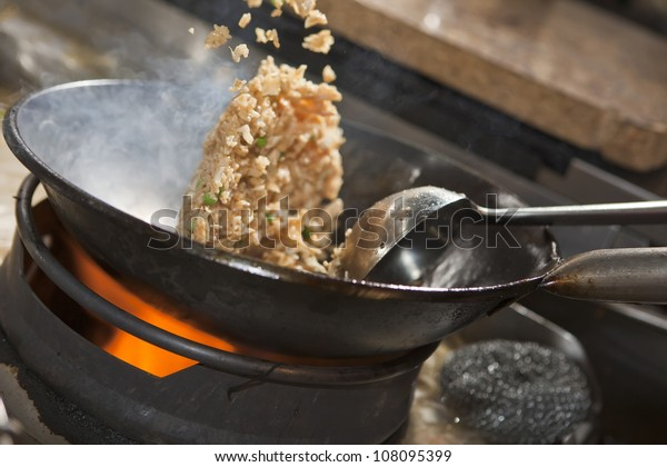 Closeup of steaming food being cooked in wok. Shallow depth of field