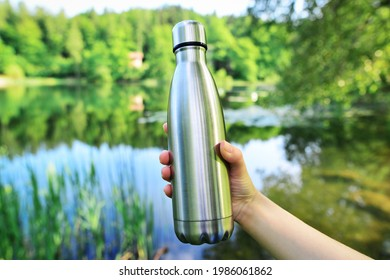 Close-up of steel eco thermo water bottle on the background of the lake in the mountains. Copy space. Zero waste, no plastic, sustainability.