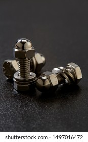 Close-Up of steel nut and bolt sat on black background, copy space for text