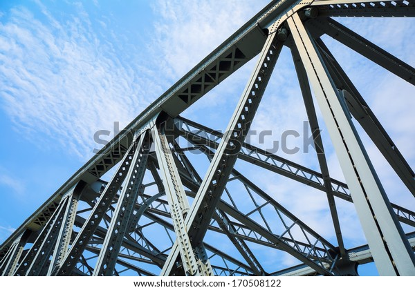 closeup of the steel structure bridge against a blue sky