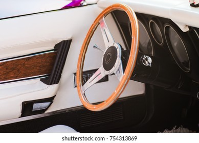 Close-up of a steering wheel of a vintage car with white leather interior. Classic retromobile details.