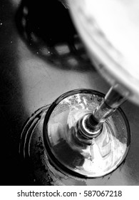 Closeup of stem beer glass in bar in black and white