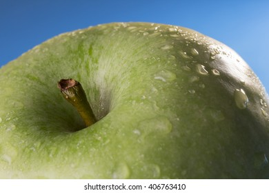 Close-up of the stem of a green apple with water drops