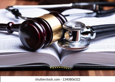 Close-up Of Stethoscope And Mallet Over Opened Law Book On Wooden Desk