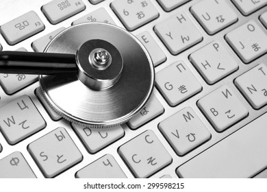 Close-up Of Stethoscope And Multilingual  Wireless Keyboard Background. Technical Support Or Repair Service Or Data Storage Or Information Security Concept
