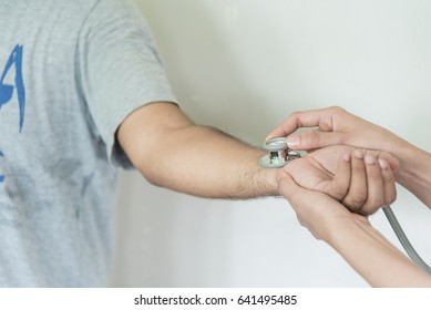 Closeup of stethoscope on patient's hand.