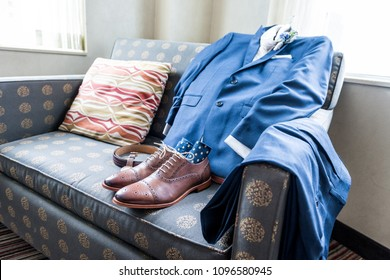 Closeup still life arrange on blue couch with Men's leather new brown shoes, socks, watch, suit for getting ready wedding preparation in room