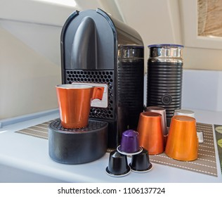 Closeup still life of espresso coffee maker machine with mug cups and capsule pods