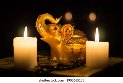 Close-up still life with a figurine of an Indian golden elephant and burning candles