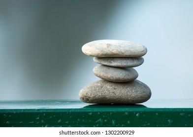 Closeup of stone balance on metallic fence in border river