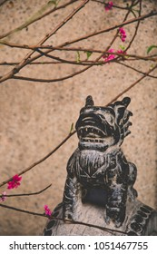 closeup of stone guardian lion and peach blossoms