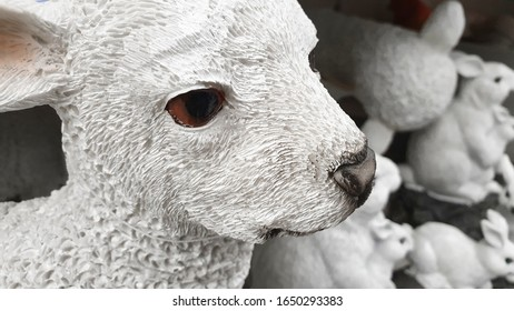 Close-up of stone lamb figurine, traditional Easter home decoration, in background a group of stone rabbits out of focus.