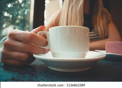 Close-up of a stone table with a cup of coffee and a delicious piece of cake. Model holds the mug and enjoys. Fashionable new interior. Perfect background for websites or coffee shops
