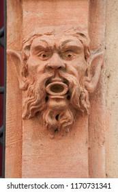 closeup stoned head on building facade