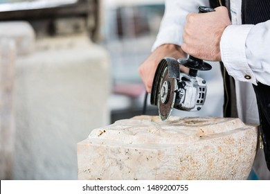Close-up of stonemason cutting marble with angle grinder