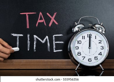Close-up Of Stopwatch In Front Of Tax And Time Concept On Blackboard