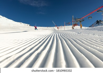 Close-up straight line rows of freshly prepared groomed ski slope piste with bright shining sun and clear blue sky background. Snowcapped mountain downhill landscape at europe winter skiing resort