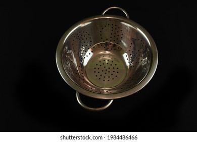 A closeup of a strainer on a black background