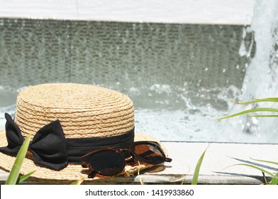 Close-up of a straw hat with a black bow and dark sunglasses with a fountain on a background