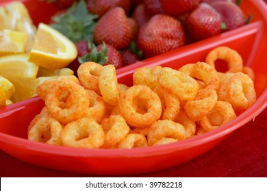 Close-up of strawberries, lemon slices, and cheese curls in a divided bowl. Horizontal format.
