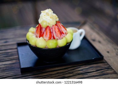 Closeup strawberry melon milk Bingsu or Bingsoo on tray put on wooden table in restaurant, popular Korean shaved ice dessert with whipped cream, strawberry and melon toppings.