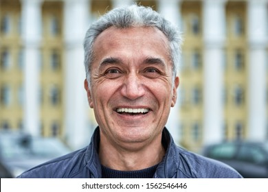 Close-up street portrait of a joyful successful intelligent middle-aged man with delicate facial features. A male older than 50, looking like a politician or a military man, laughs outdoors.