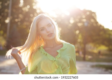 Closeup street portrait of a luxurious elegant woman with long hair walking at sunset. Space for text