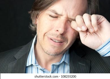 Nahaufnahme eines gestressten Geschäftsmanns, der sich die Augen rieb.