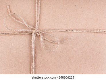 Closeup of string tied into a bow around a package wrapped in plain brown paper
