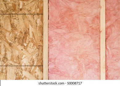 Close-up of strips of pink fiberglass insulation in a wall of a new building. Horizontal shot.