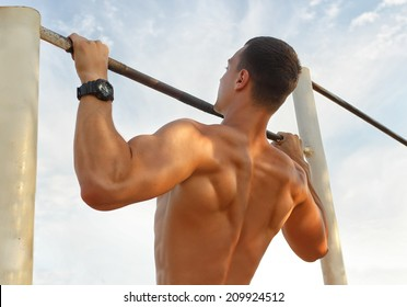 Closeup of strong  athlete doing pull-up on horizontal bar.Mans fitness with blue sky in the background and open space around him