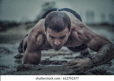 Closeup of strong athletic man crawling in wet muddy puddle in the rain in an extreme competitive sport