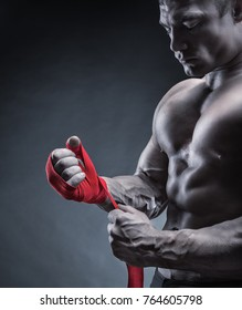 Close-up of a strong boxer putting on red straps and getting ready to fight
